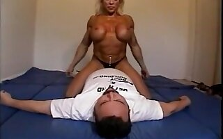 Nude female bodybuilder dominates male with scissors, facesits, ass smothers and breast