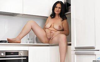 Solo mature brunette Ria Black drops her clothes in the kitchen